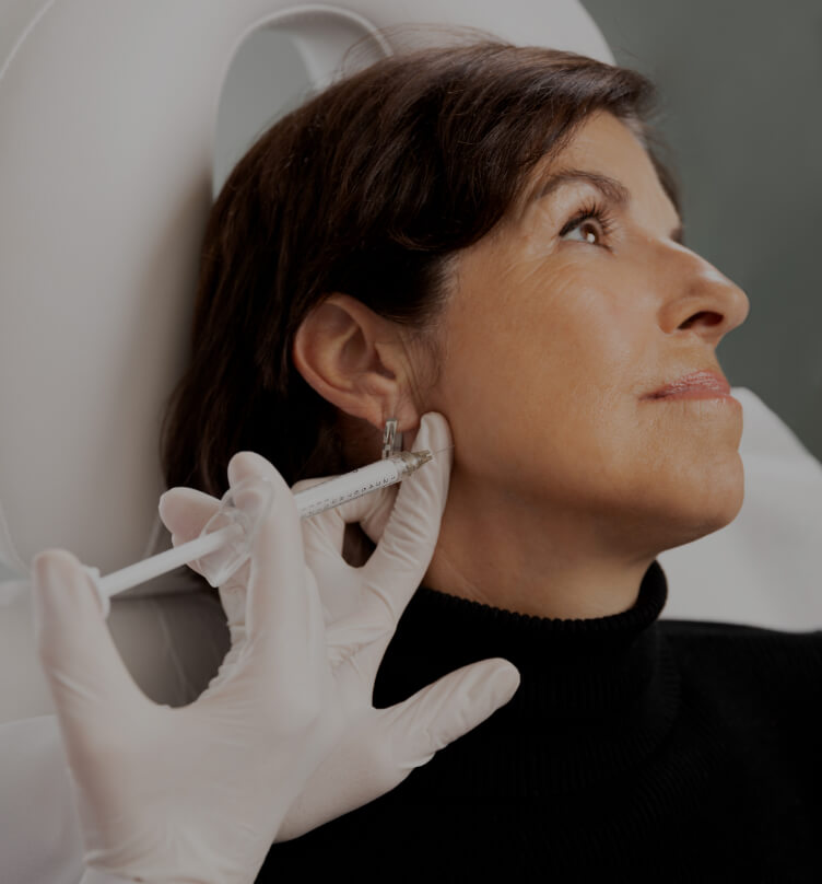 A doctor from Clinique Chloé doing Radiesse injections into a female patient's jawline