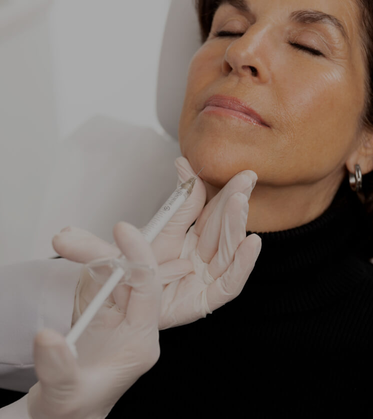 A doctor from Clinique Chloé doing Radiesse injections into a female patient's chin