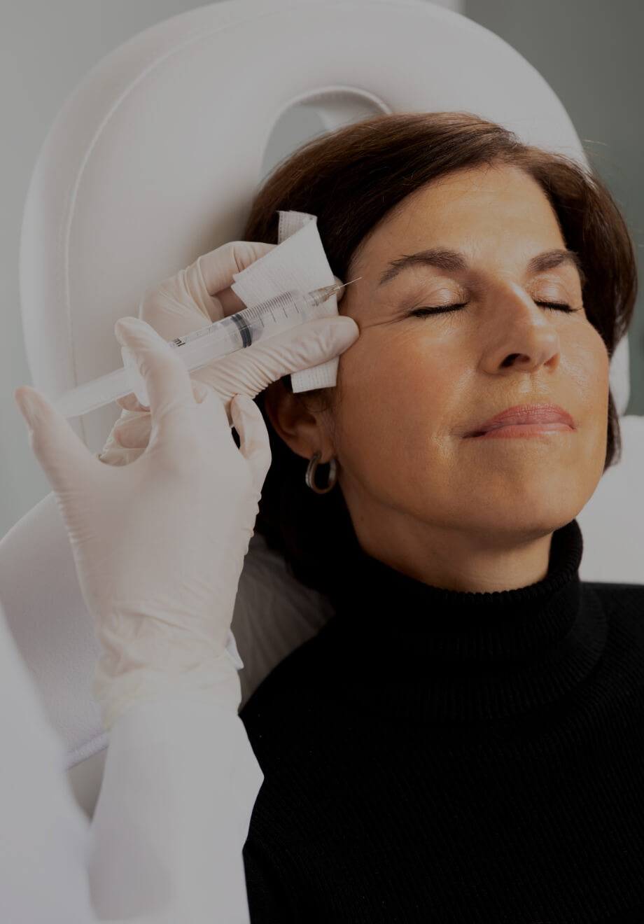 A doctor at Clinique Chloé performing Sculptra injections in a female patient's temples