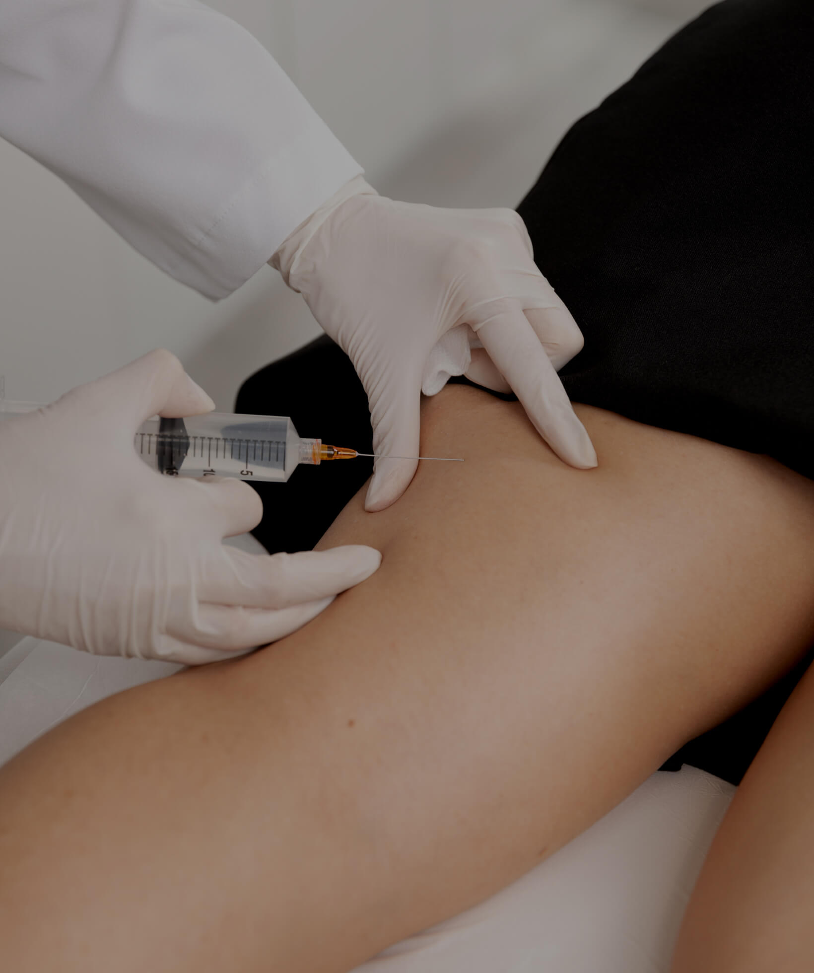 A doctor at Clinique Chloé performing Sculptra injections in a female patient's thighs