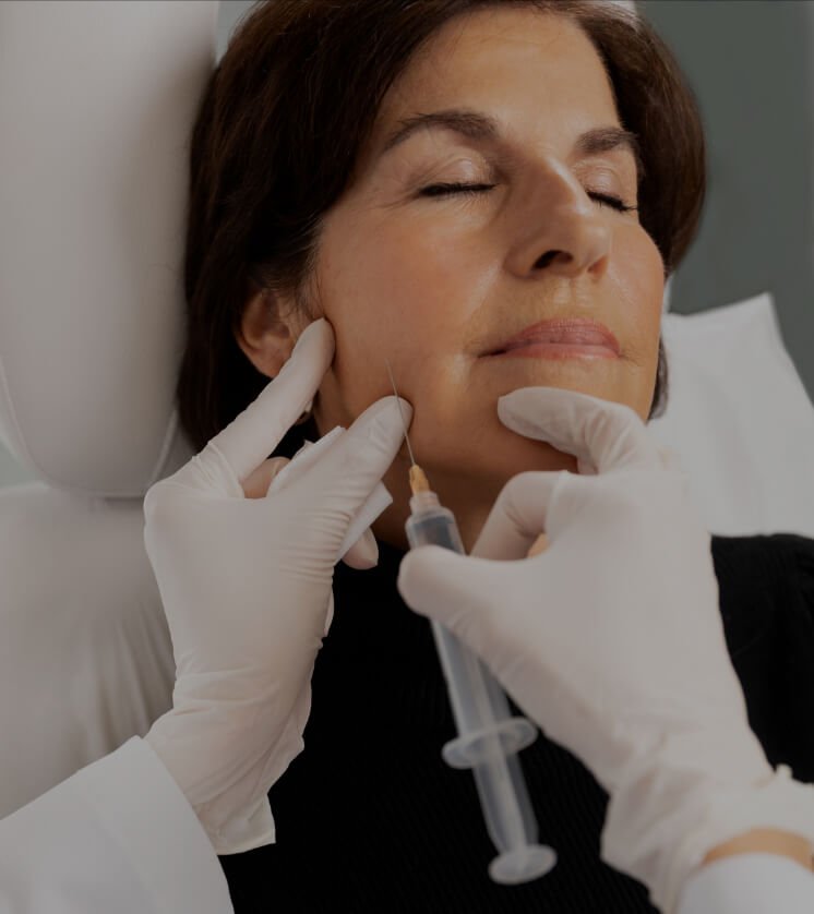 A doctor at Clinique Chloé performing Sculptra injections in a female patient's jawline