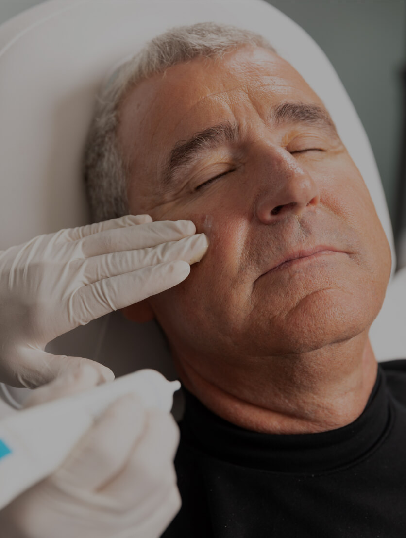 A technician at Clinique Chloé applying soothing cream to a patient's face after a chemical peel